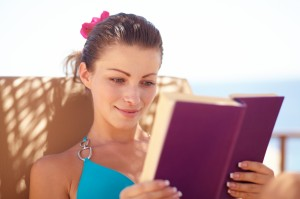Pretty young female reading a book while lying by the beach