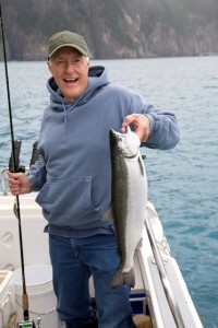 Happy fisherman in Alaska holds big silver salmon