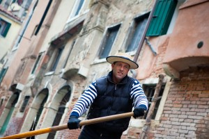 Gondolier navigates on the channel of Venice