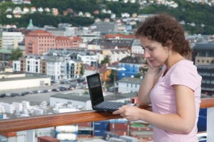 Girl standing on deck of ship learned on railing and looking at laptop in Bergen, Norway