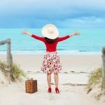 beautiful woman traveler in retro style dress  on the beach